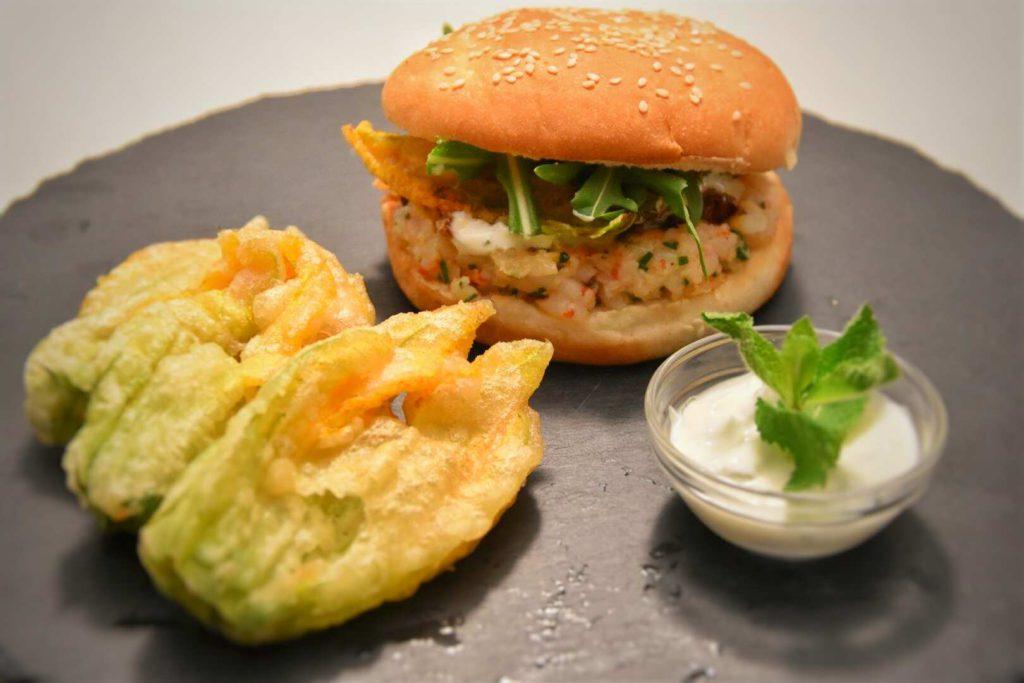 hamburger di gamberi con cipollotto caramellato, fiori di zucchina e rucola