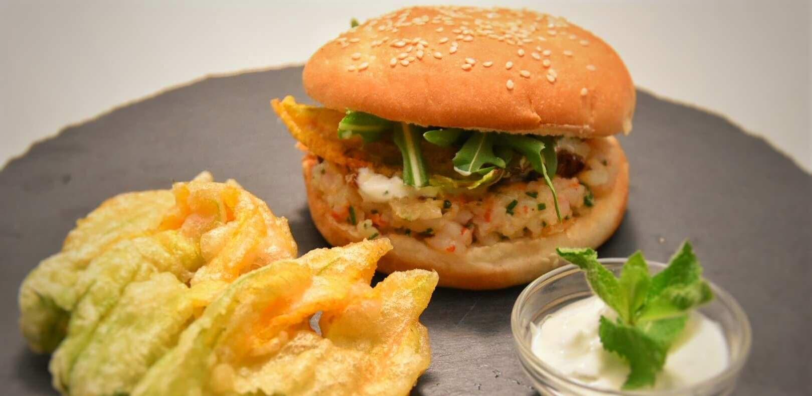 Hamburger di gamberi, cipollotto caramellato, fiori di zucchina croccanti e rucola