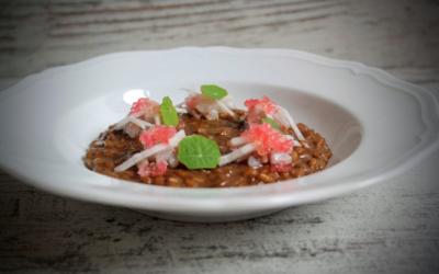 Risotto all'aglio nero fermentato, tartare di branzino, rapa bianca marinata e fingerlime